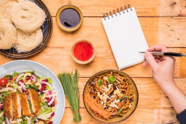 Close-up, de, um, pessoa, escrita, ligado, notepad, com, caneta, perto, a, comida tailandesa, ligado, tabela madeira Foto gratuita