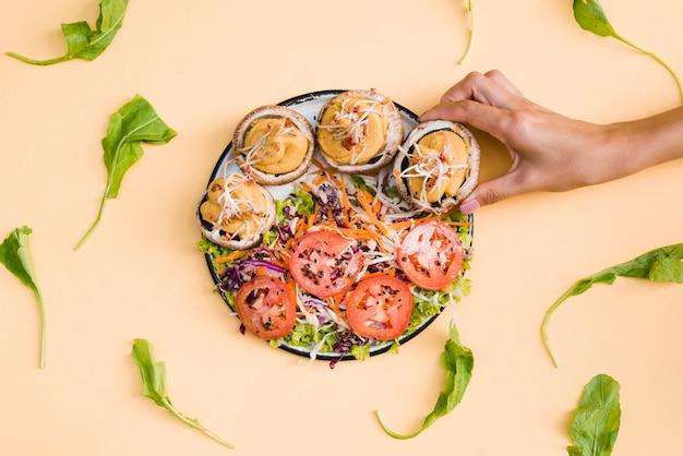 Close-up, de, um, pessoa, levando, cogumelos, bonés, recheado, com, natas, ligado, prato, sobre, a, bege, fundo Foto gratuita