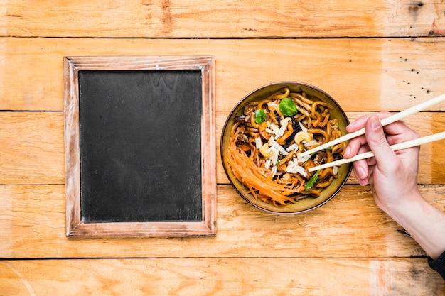 Close-up, de, um, pessoa, mão, colheita, a, noodles, com, chopsticks, perto, a, em branco, ardósia, ligado, tabela Foto gratuita