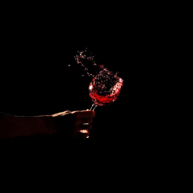 Close-up, de, um, pessoa, mão, copo segurando, de, vinho tinto, respingue, de, vidro Foto gratuita