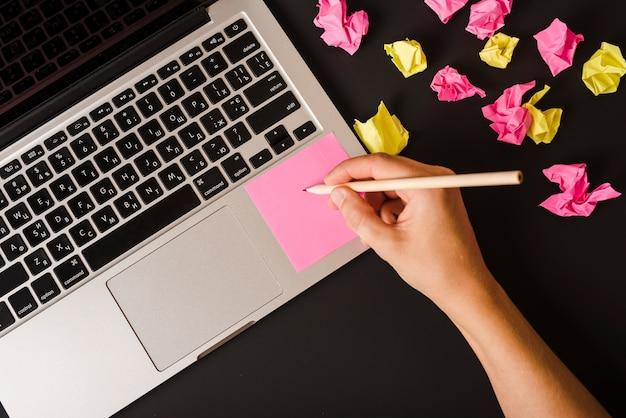 Close-up, de, um, pessoa, mão, escrita nota adesiva rosa, ligado, laptop, contra, experiência preta Foto gratuita