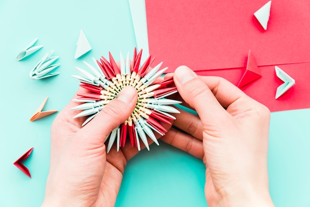 Close-up, de, um, pessoa, mão, fazer, a, papel, flor, ligado, cerceta, fundo Foto gratuita