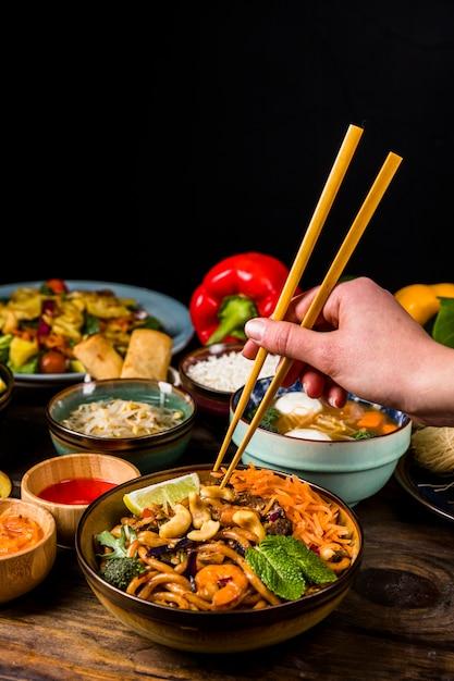 Close-up, de, um, pessoa, mão, levando, comida tailandesa, com, chopsticks, contra, experiência preta Foto gratuita