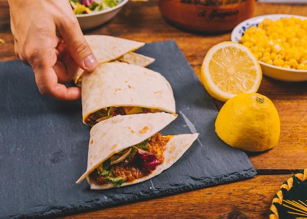 Close-up, de, um, pessoa, mão, levando, fatia, de, um, mexicano, tacos carne Foto gratuita