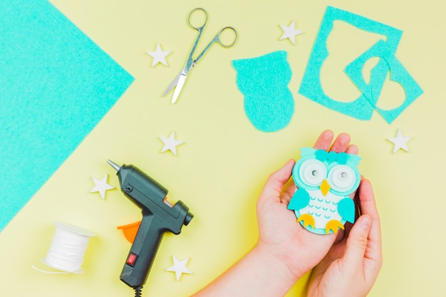 Close-up, de, um, pessoa, mão, mostrando, handmade, papel azul, cute, coruja, ligado, amarela, fundo Foto gratuita