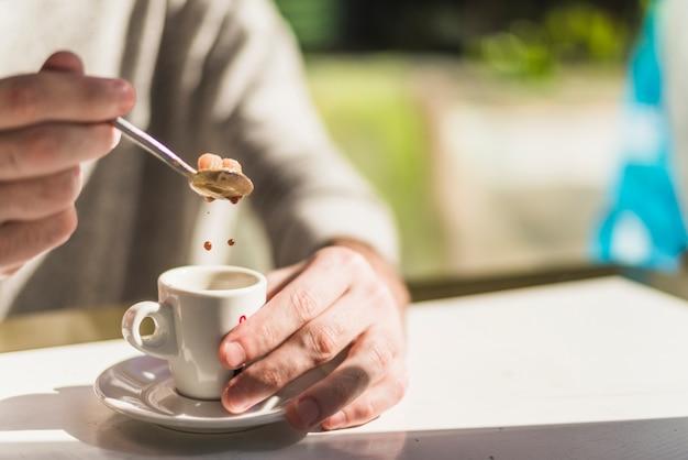 Close-up, de, um, pessoa, mão, pôr, açúcar mascavo, em, a, vermelho, chá herbóreo Foto gratuita