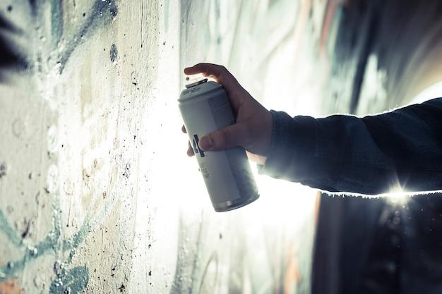 Close-up, de, um, pessoa, mão, quadro, graffiti, com, pulverize lata, ligado, parede Foto gratuita
