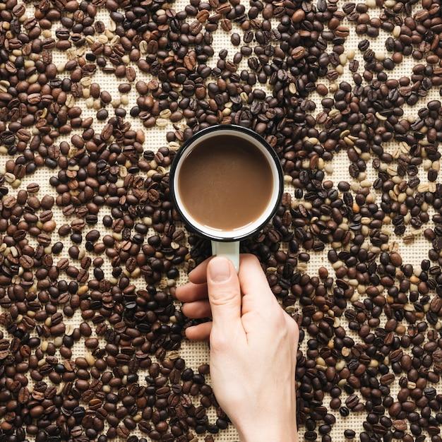 Close-up, de, um, pessoa, mão segura xícara, de, um, café, cercado, por, feijões café Foto gratuita