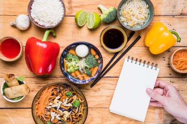 Close-up, de, um, pessoa, mão, segurando, espiral, notepad, com, alimento tailandês, ligado, tabela Foto gratuita