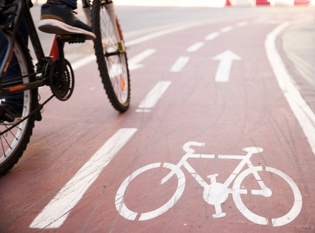 Close-up, de, um, pessoa, montando, a, bicicleta, ligado, a, ciclo, pista Foto gratuita