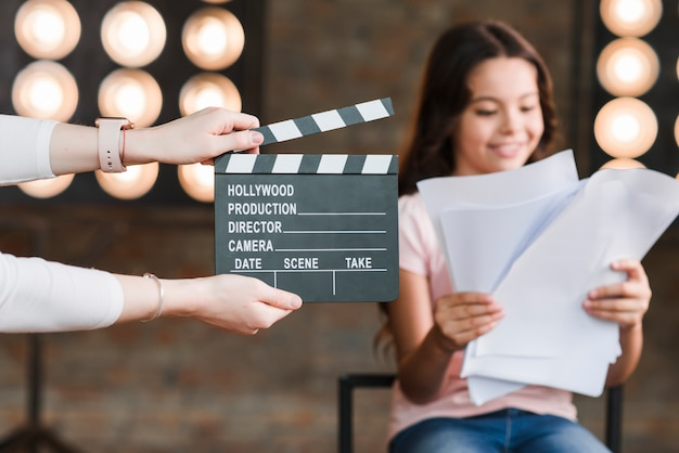 Close-up, de, um, pessoa, segurando, clapper, borda, frente, menina, leitura, scripts Foto gratuita
