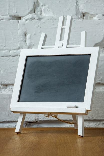 Close-up de um quadro de giz miniatura com manchas de giz e giz em uma parede de tijolos brancos Foto Premium