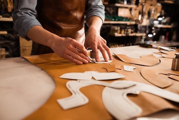 Close-up de um sapateiro medir e cortar couro Foto gratuita