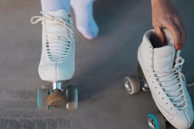Close-up, de, um, skater feminino, removendo, a, patim rolo Foto gratuita