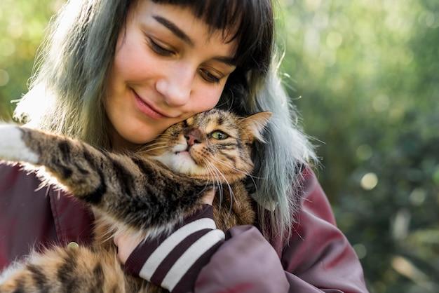 Close-up, de, um, sorrindo, mulher bonita, abraçar, dela, gato malhado, em, jardim Foto Premium