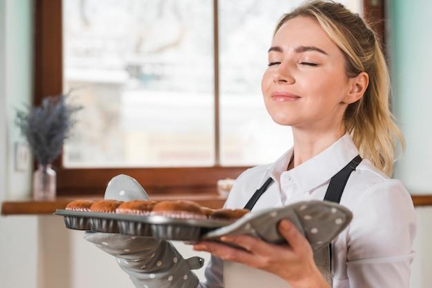 Close-up, de, um, sorrindo, mulher jovem, cheirando, a, fresco, assado, muffins Foto gratuita