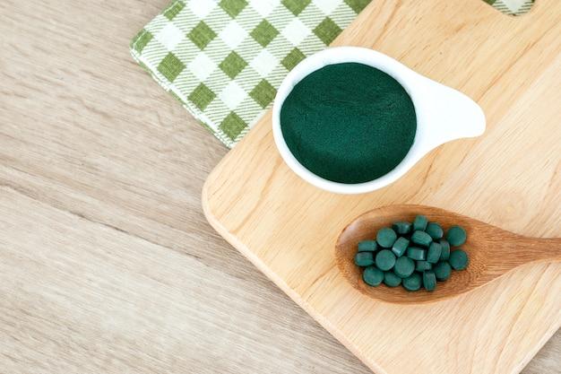 Close up de um spirulina em pó e spirulina comprimidos em colher, dieta saudável superalimento e uma nutrição de desintoxicação Foto Premium