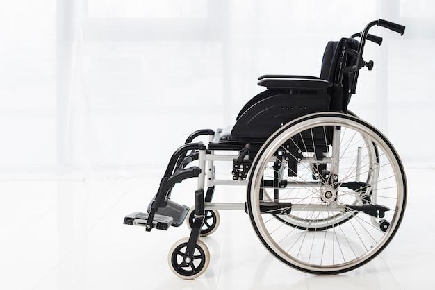 Close-up, de, um, vazio, cadeira rodas, em, um, sala, com, branca, cortina Foto gratuita