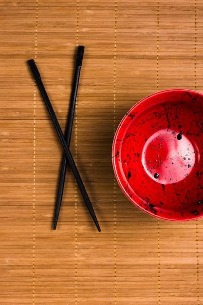 Close-up, de, um, vazio, tigela vermelha, com, molho soja, manchas, e, pretas, chopsticks, ligado, marrom, placemat, fundo Foto gratuita