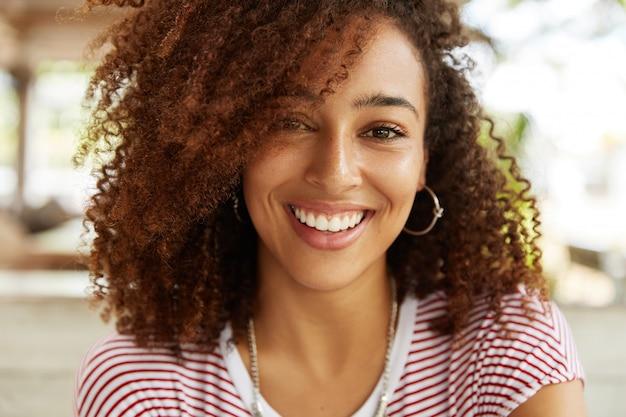 Close up de uma adorável mulher afro-americana com um sorriso largo, vestindo uma camiseta listrada, estando de bom humor, descansando no refeitório com os melhores amigos. mulher jovem sorridente de pele escura em poses internas Foto gratuita