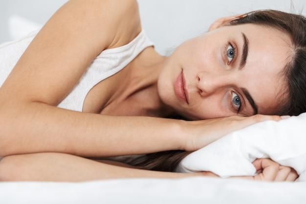 Close-up de uma bela jovem relaxando na cama em casa Foto Premium
