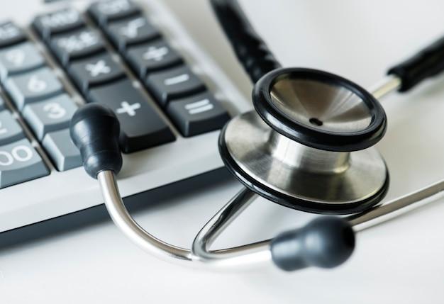 Close up de uma calculadora e um conceito de cuidados de saúde e despesas de estetoscópio Foto gratuita