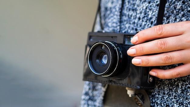 Close-up de uma câmera fotográfica retrô realizada por uma mulher Foto gratuita