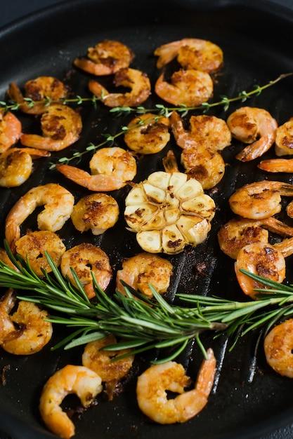 Close-up de uma frigideira com os camarões fritados do rei e os ramos dos alecrins e do tomilho. Foto Premium