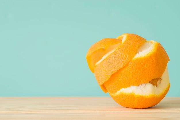 Close-up de uma fruta laranja descascada na superfície de madeira Foto gratuita