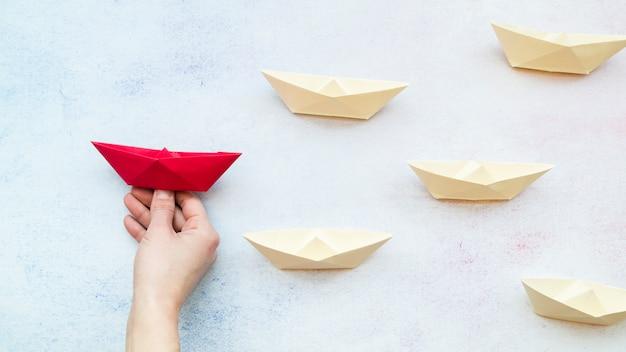 Close-up de uma mão de pessoa segurando o barco vermelho entre os barcos de papel branco no pano de fundo texturizado azul Foto gratuita