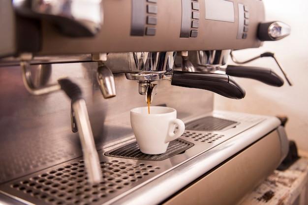 Close-up de uma máquina de café expresso que faz uma xícara de café. Foto Premium