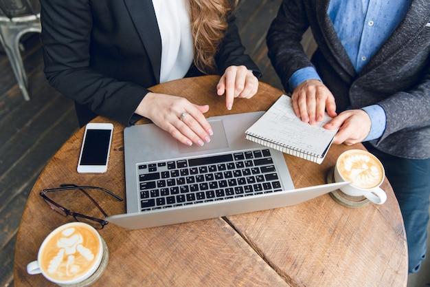 Close-up de uma mesa de centro com dois colegas sentados segurando um caderno e digitando no laptop Foto gratuita