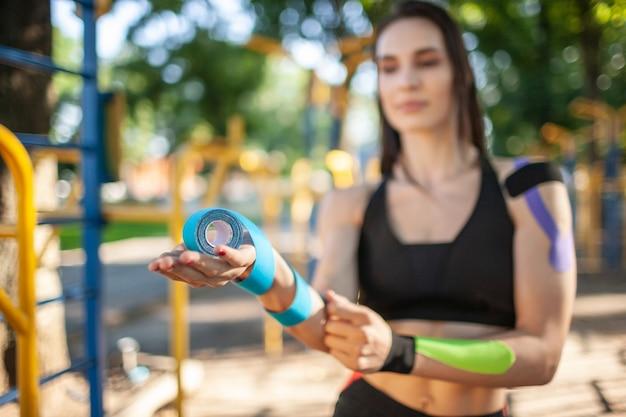 Close-up de uma mulher desfocada segurando rolos coloridos de fitas elásticas de cinesiologia Foto Premium