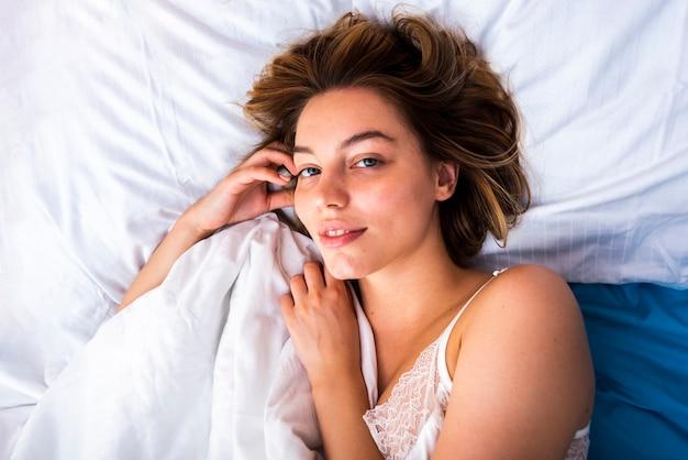 Close-up de uma mulher despertar, olhando para a câmera Foto gratuita