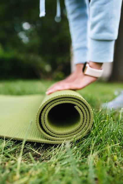 Close-up de uma mulher dobrando roll fitness ou tapete de ioga após malhar no parque Foto gratuita