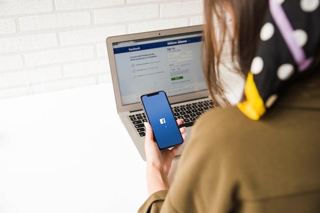 Close-up de uma mulher tentando fazer logon no aplicativo do facebook no celular e laptop Foto gratuita