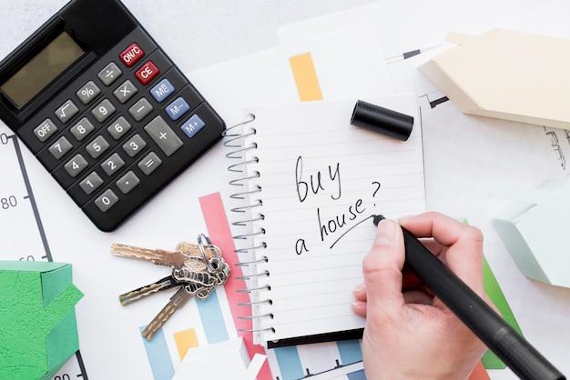 Close-up de uma pessoa escrevendo para comprar uma casa no bloco de notas em espiral com chaves; calculadora e modelo de casa Foto gratuita