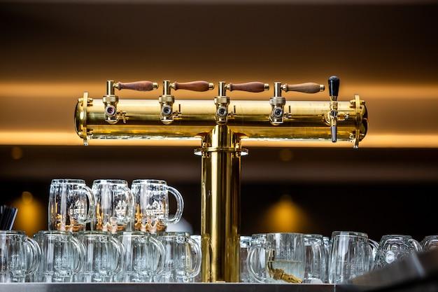 Close up de uma torneira de cerveja ou torneira com grande arrenge de um copo vazio no bar ou pub, conceito de restaurante Foto Premium