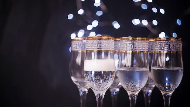 Close-up, de, vidro transparente, com, champanhe, contra, escuro, bokeh, fundo Foto gratuita