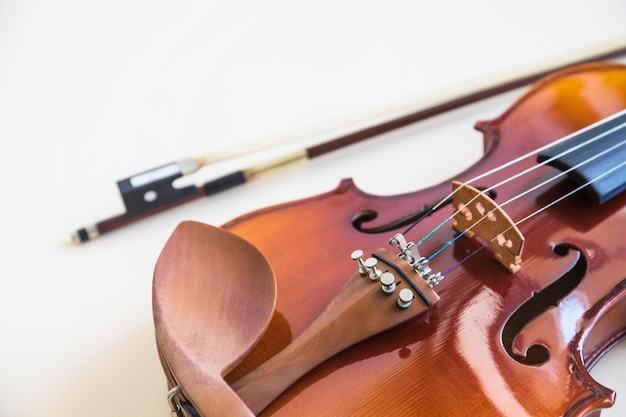 Close-up, de, violino, cadeia, com, arco, branco, pano de fundo Foto gratuita
