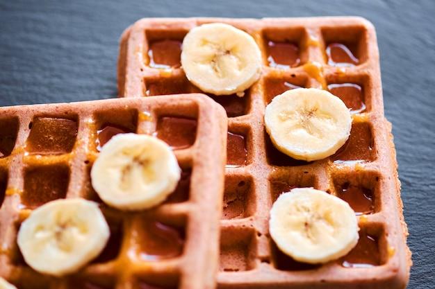 Close-up de waffles com banana e mel Foto Premium