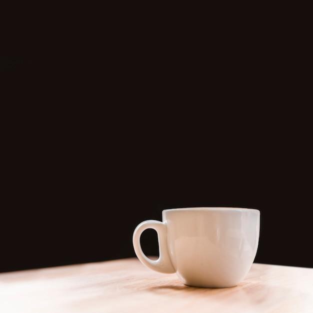 Close-up, de, xícara branca café, escrivaninha, sobre, pretas, fundo Foto gratuita