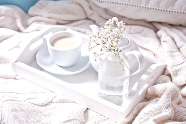 Close-up de xícara de chá, leite, bule e buquê Foto Premium