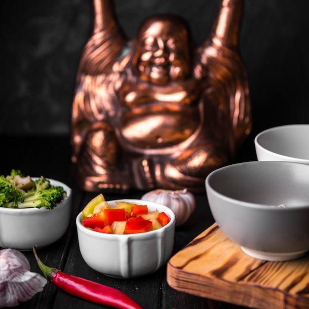 Close-up de xícaras de legumes com estátua Foto gratuita