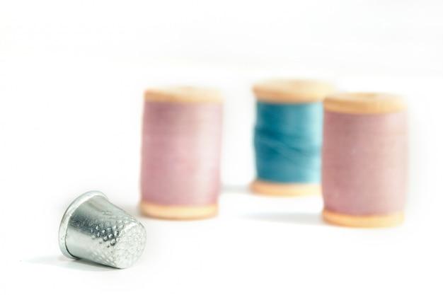 Close-up dedal com carretéis de linha em foco suave, isolado no fundo branco Foto Premium