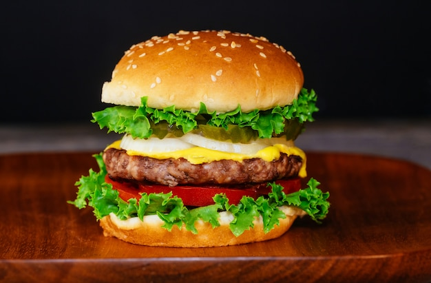 Close-up delicioso hamburguer fresco placa de madeira Foto Premium