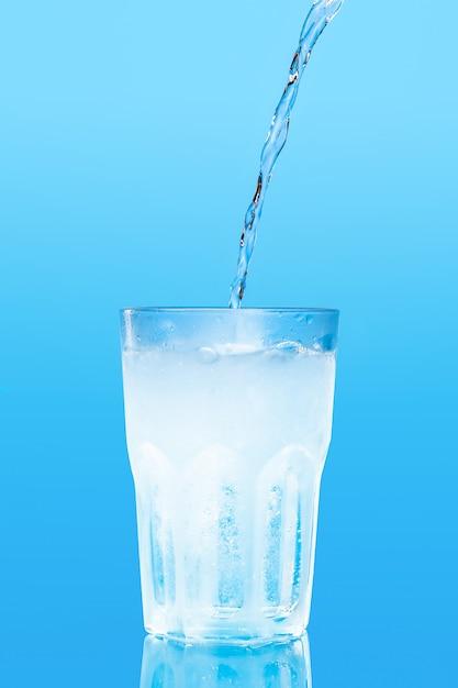 Close-up derramando purificada água de bebida fresca da garrafa na mesa Foto Premium