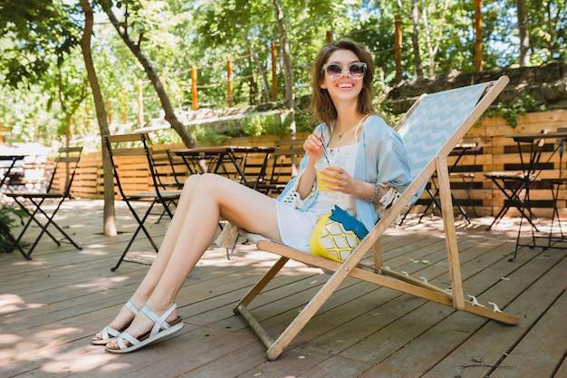 Close-up detalhes de jovem sentada na cadeira de praia em roupa de moda de verão, vestido branco, capa azul, bolsa amarela, bebendo limonada, acessórios elegantes, pernas muito magras em sandálias Foto gratuita