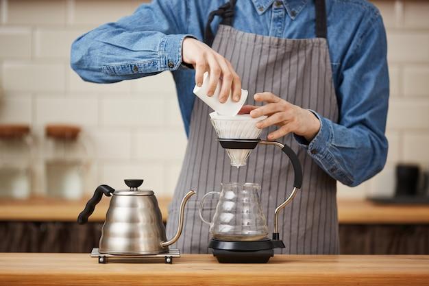Close up do barista masculino que derrama o café à terra que faz o pouron. Foto gratuita