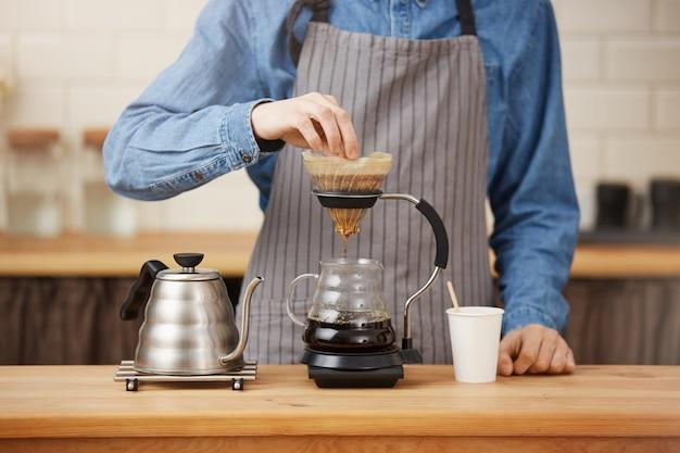 Close up do barman rofessional que prepara o café do pouron no chemex. Foto gratuita